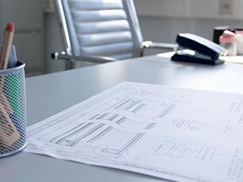 Planungssituation am Schreibtisch: Man sieht Blaupausen und Skizzen von Stahlprofilen